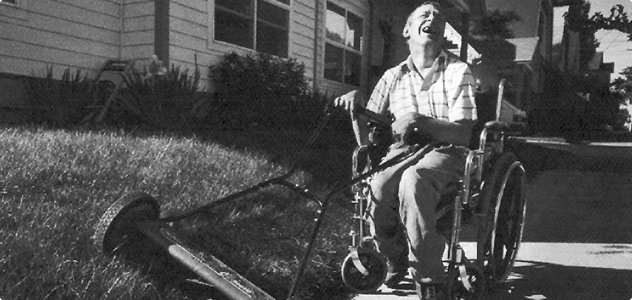 man mowing lawn in wheelchair