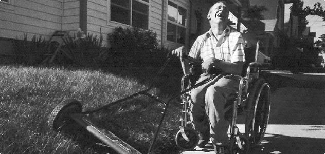 man mowing lawn in wheelchair