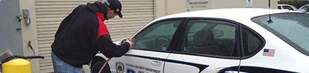 employee washing a police car